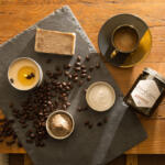National Coffee Day Coffee Bar soap, Coffee scrub and cup of coffee with buckwheat honey, haute cocoa body butter, grounded candle and coffee beans on slate on a wood table with low lighting