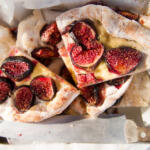 Fig Focaccia cut into pieces on parchment with knife on baking tray