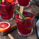 Mulled Wine glasses with rosemary garnish, sliced citrus fruit on wooden cutting board and cinnamon sticks