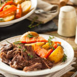 Serving of sweet classic pot roast with potatoes, carrots and a sprig of thyme in white bowl on table with salt and pepper shaker, napkin and fork