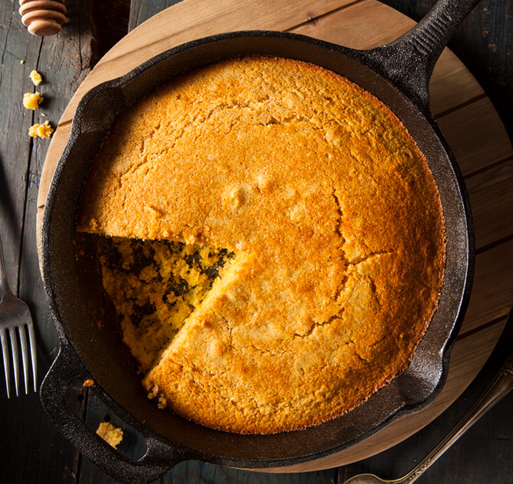 Cornbread in a round pan with a pie-shaped slice out of it still in the steel skillet.