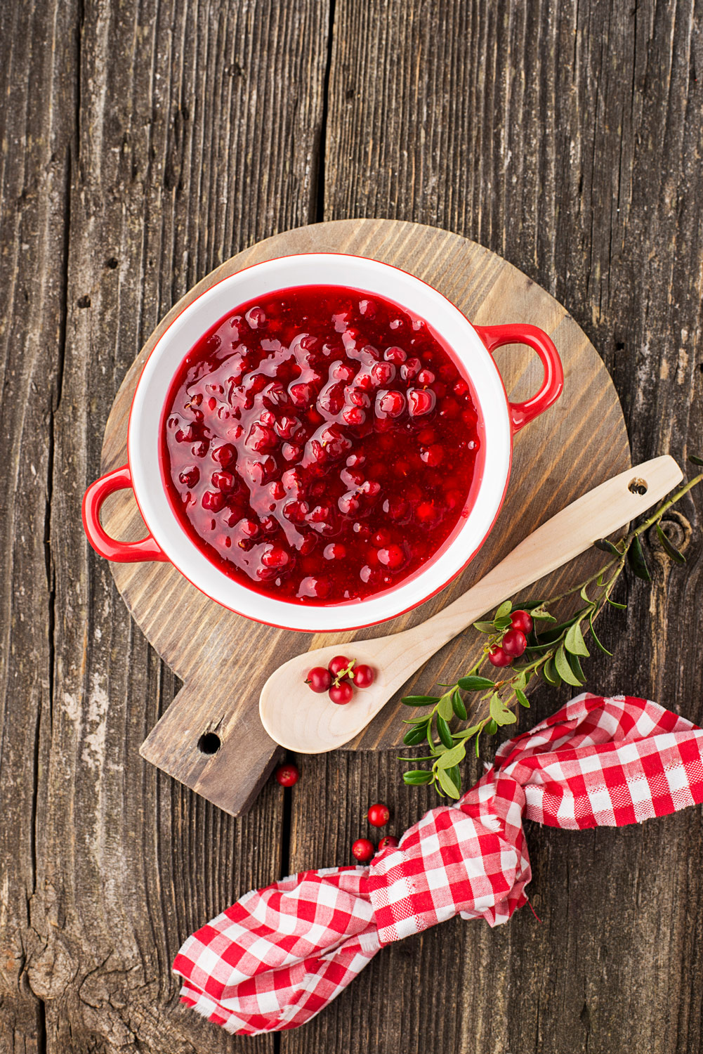 Honey Cranberry relish on cutting board on wood talbe with red gingham napkin and wooden serving spoon with cranberry garnish and sprig of holly