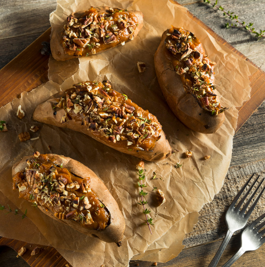 4 Baked Stuffed Sweet Potatoes topped with toasted pecans on parchment on top of cutting board on top of wooden table with forks