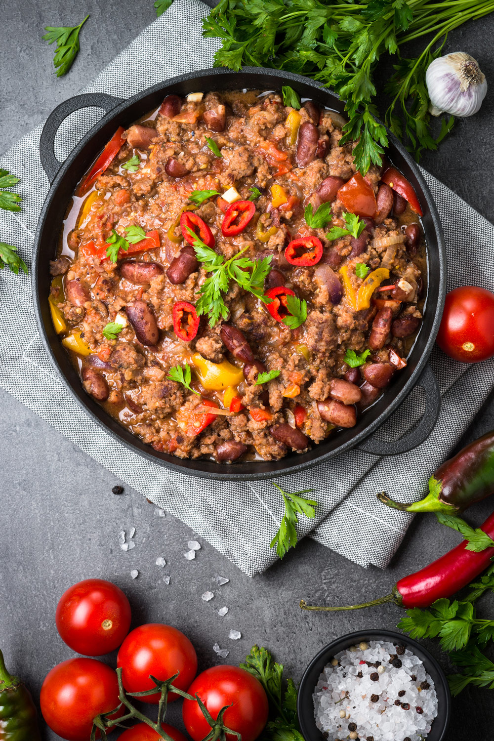 Turkey Chili in a cast iron pot on a grey napkin surrounded by parsley, fresh tomatoes, salt on a kitchen table