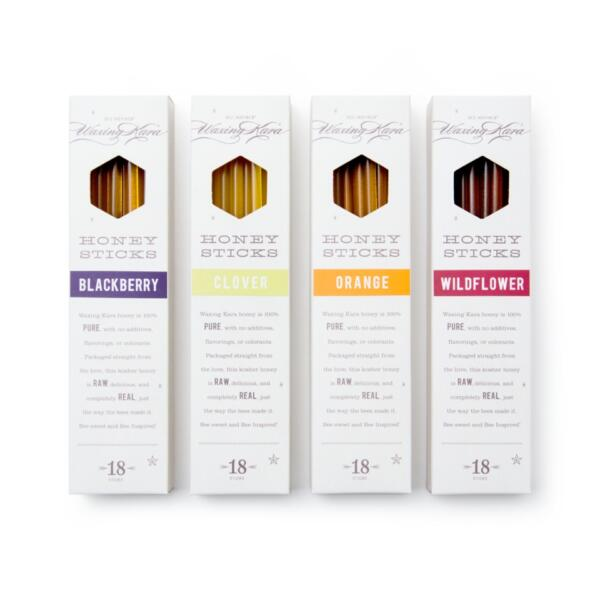 Four boxes of honey sticks in clover, orange, blackberry and wildflower on white surface