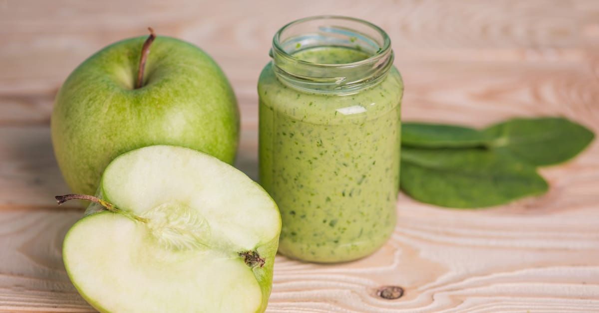 green smoothie made with green apple and spinach in mason jar on table