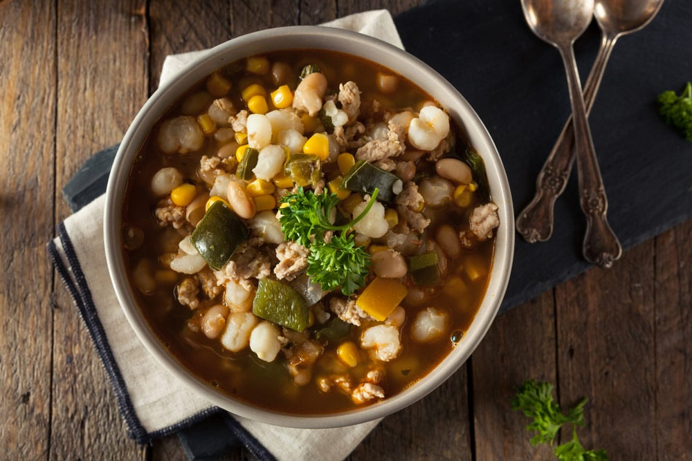 white chicken chili dish in casserole on wood table in dark setting