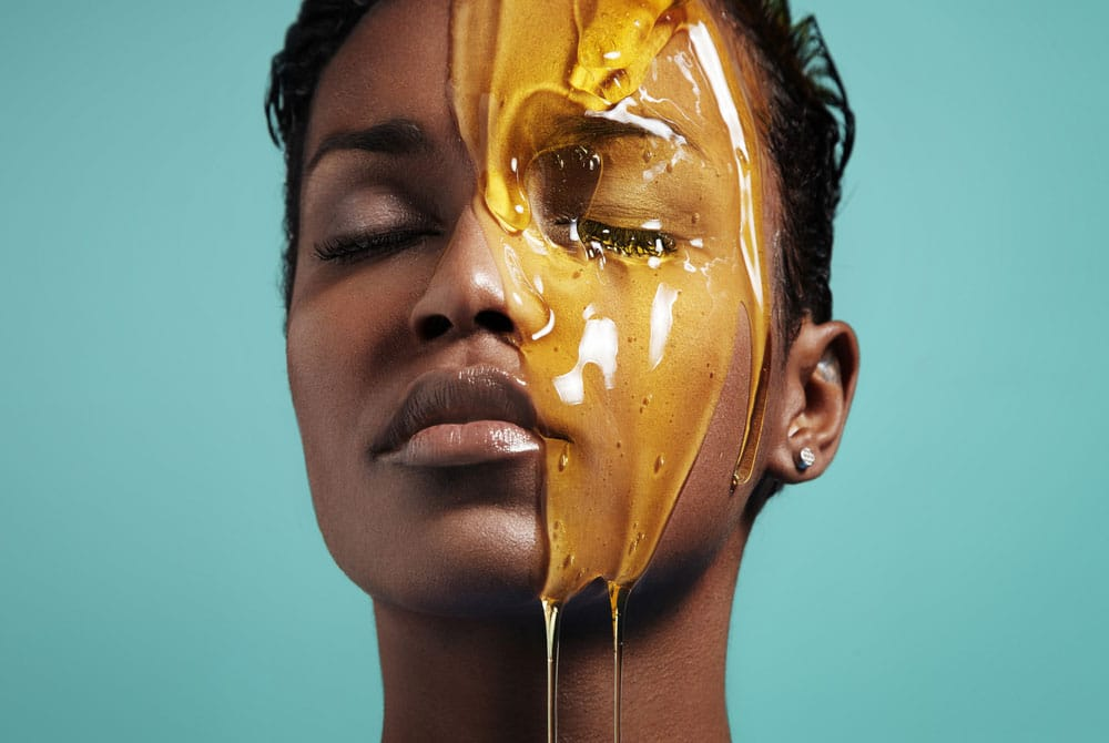 Model with eyes closed and a jar of honey on her face
