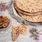 Passover Table with handmade Matzah and silver platter on white tablecloth and flowers and walnuts for making charoset