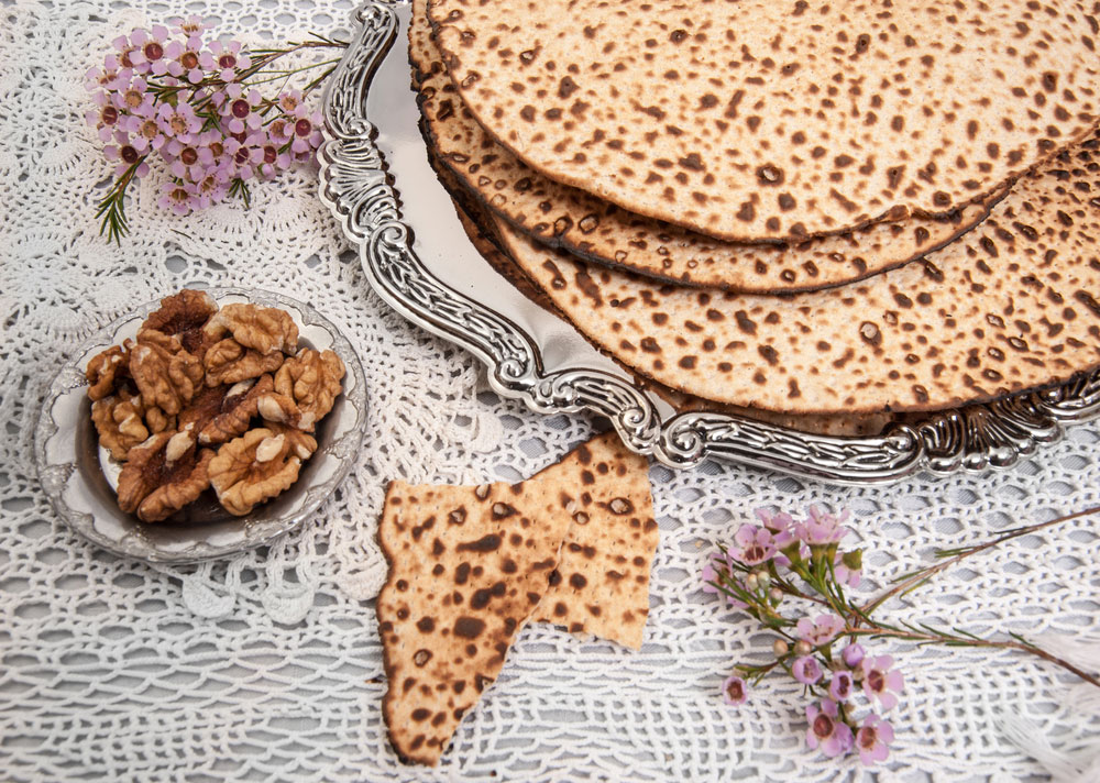 Passover Table with handmade Matzah and silver platter on white tablecloth and flowers and walnuts