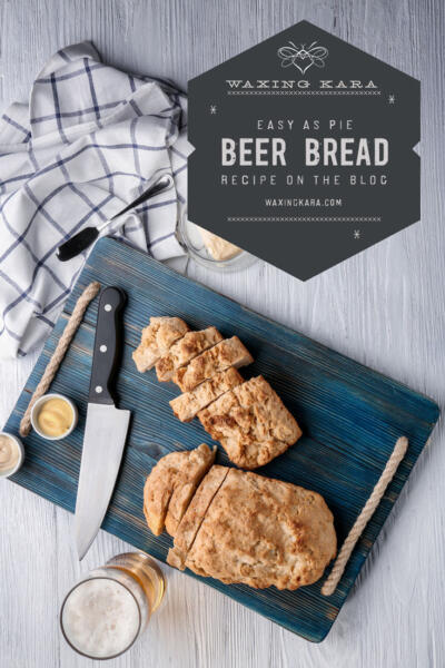 Beer Bread, sliced on cutting board with glass of beer and towel overhead on kitchen counter