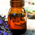 A bottle of essential oil with blossoms.