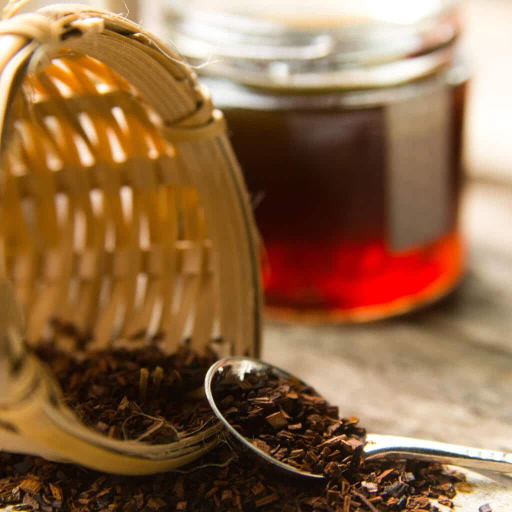 Bees Knees Artisan Tea in tea strainer with spoon and honey in the background