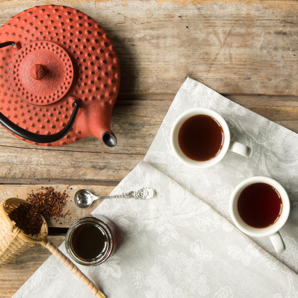 National Hot Tea Month set with red teapot 2 cups filled with hot tea and a tea basket filled with loose leaf tea on wooden table