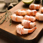 Bacon wrapped shrimp on cutting board raw and ready to be grilled