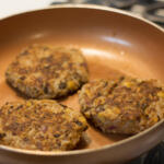 three black bean burgers with honey in pan