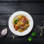 Asian Noodle Salad on black table with fresh vegetables surrounded by raw ingredients