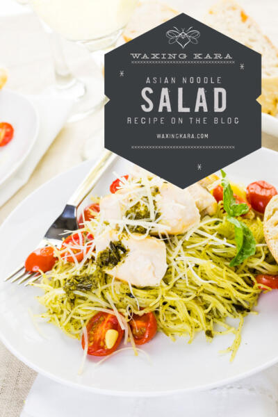 Asian noodle salad with grilled chicken and cherry tomatoes on white plate on kitchen table with wine glass