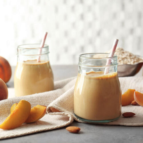 Peach Smoothie with fresh peaches and raw oats in glass jars with straws
