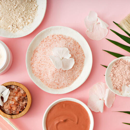 Raw ingredients for the bee well DIY face mask including clay oats and salts on pink table with palm leaf and paint brush