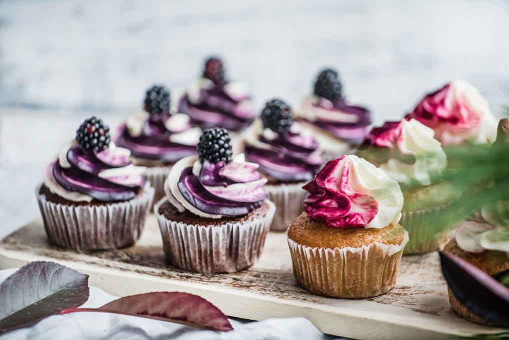 blackberry topped cupcakes on rustic tray with some greenery as garnish