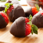 Chocolate dipped strawberries on wooden cutting board with stems showing