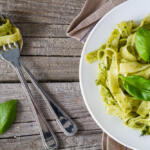 lemon pesto sauce on tagliatelle with basil leaves and a fork and spoon on a rustic wood table