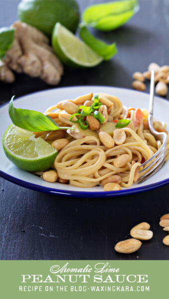 Aromatic Lime Peanut Sauce with pasta and raw peanuts on white plate on table surrounded by ingredients tall pin