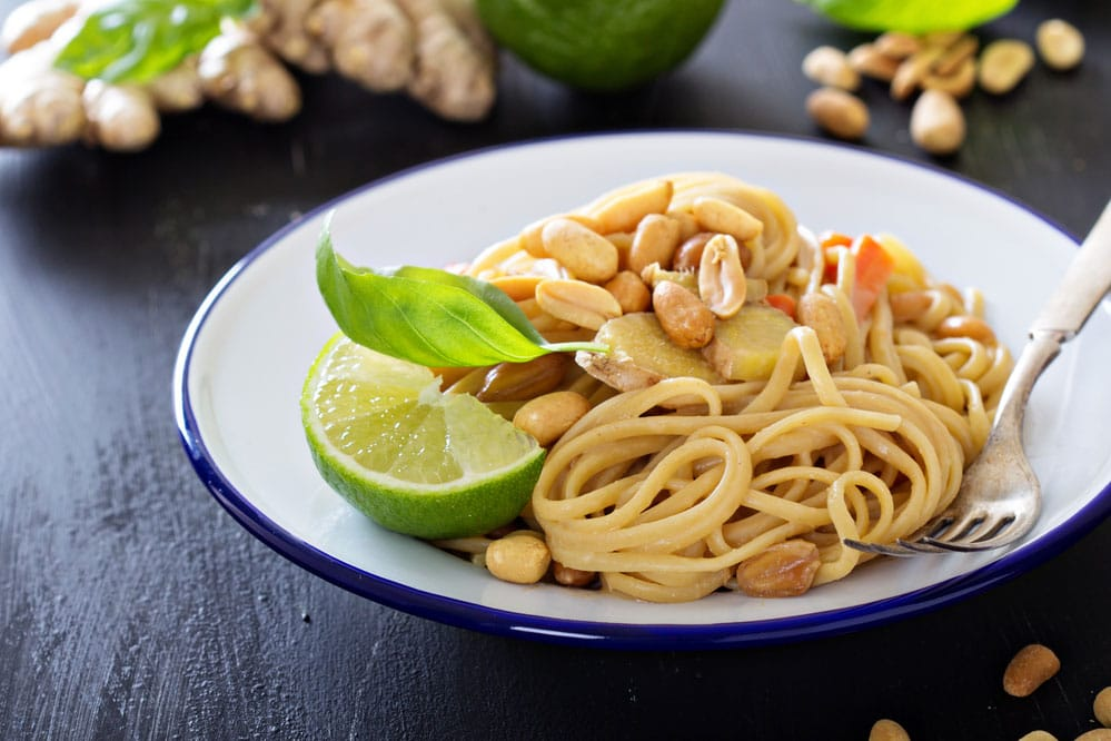 Aromatic Lime Peanut Sauce with pasta and raw peanuts on white plate on table surrounded by ingredients