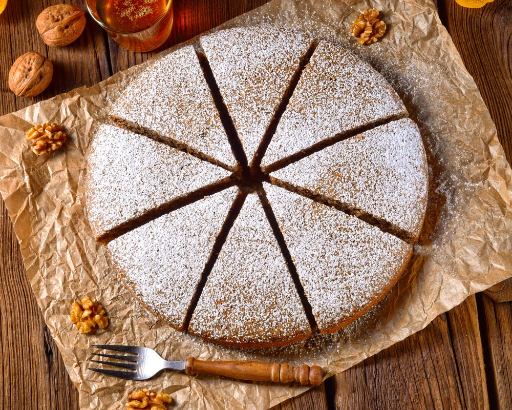 fresh baked round gingerbread cut into 8 pieces topped with powdered sugar on top of parchment on wooden table surrounded by raw ingredients for muriel's gingerbread recipe