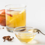 Fresh made Apple Cider Vinegar Honey Detox drink with raw ingredients on white table