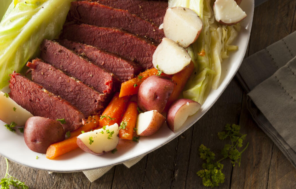Glazed Corned Beef on platter surrounded by cabbage, potatoes and carrots ready for serving