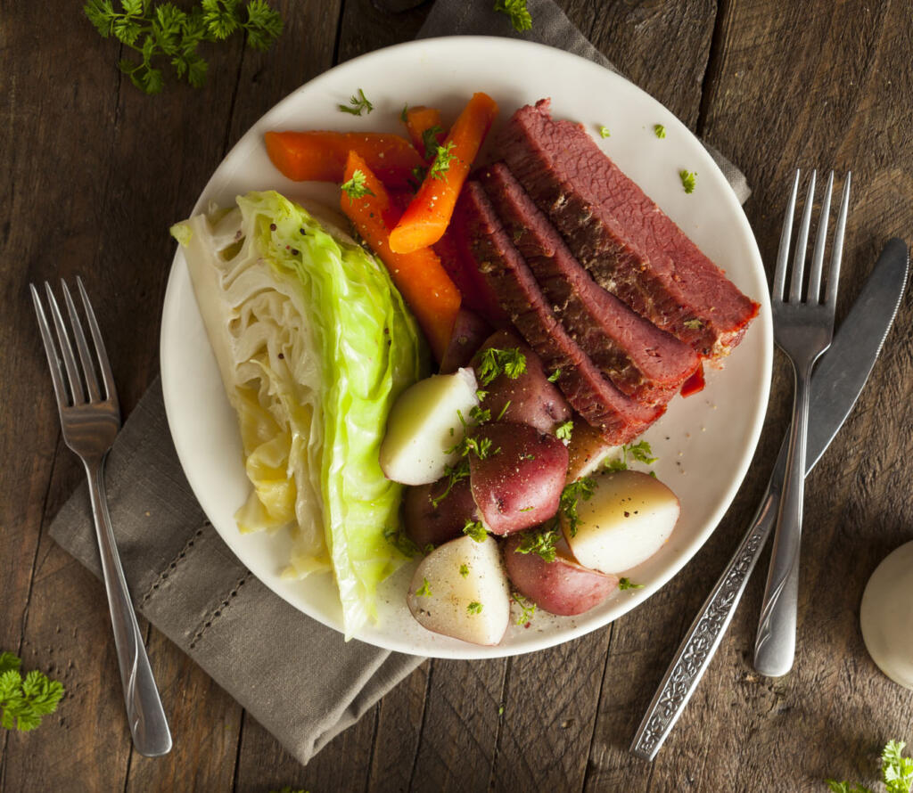 Glazed Corned beef and cabbag on dinner plate on dinner talble with napkin fork and knife