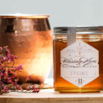 Honey Moscow mule on wooden board in copper cup next to Waxing Kara Spring Honey