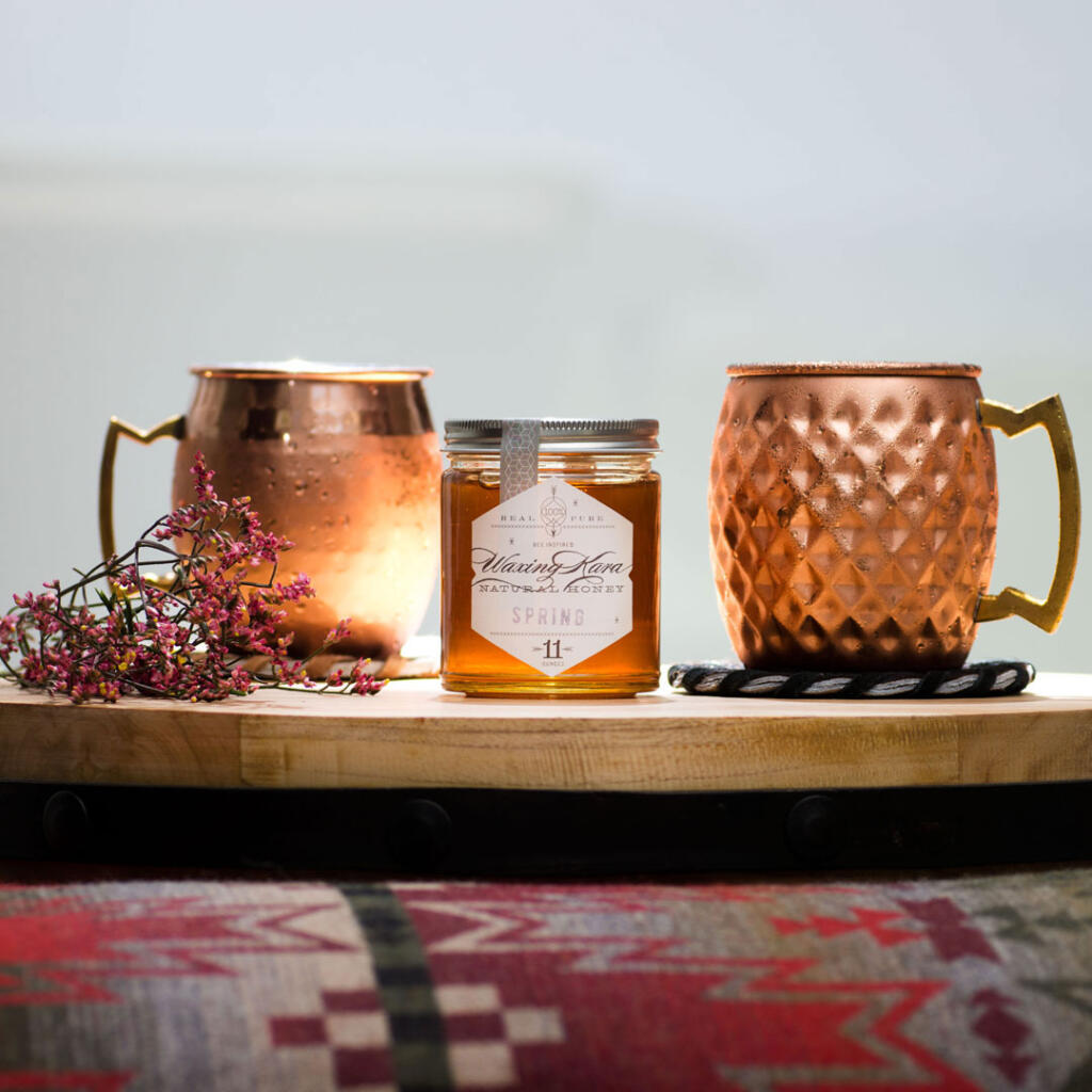 Honey Moscow Mule on wood tray in copper mugs accompanied by Waxing Kara Spring Honey