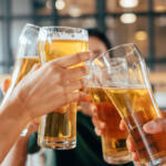 National Beer Day toast among friends at bar hands holding tall beer glasses