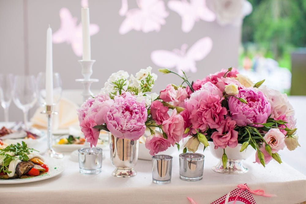 Wedding Season table setting with beautiful pink flowers and white table-covering with candles and bee and butterfly decorations on the wall