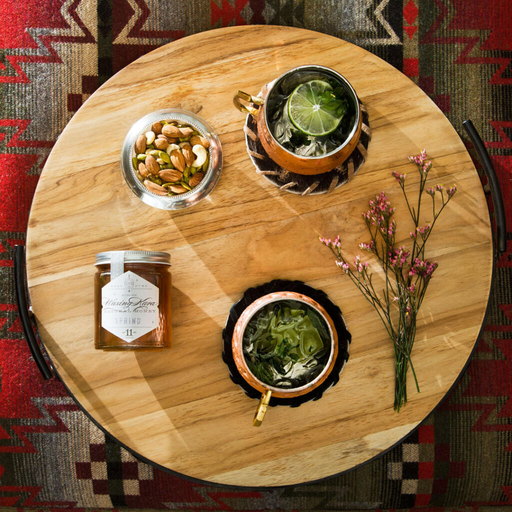 honey moscow mule with jar of honey, flowers and nuts in copper mugs on wood tray overhead