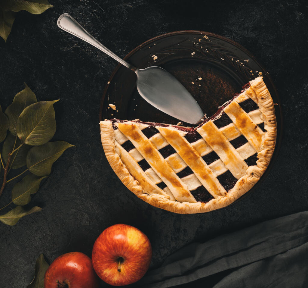 Old Fashioned Apple Pie with slices missing and a cake cutter on dark table accompanied by whole apples and fabric in honor of national apple pie day