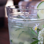 Cucumber Gin Cocktail with Honey closeup with sweat and cucumber garnish