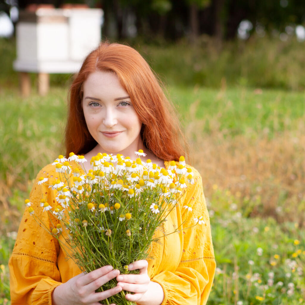 Kaylin holding a bunch of chamomile flowers