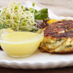 maryland crab cakes prepared and cooked on plate with dipping sauce next to green salad