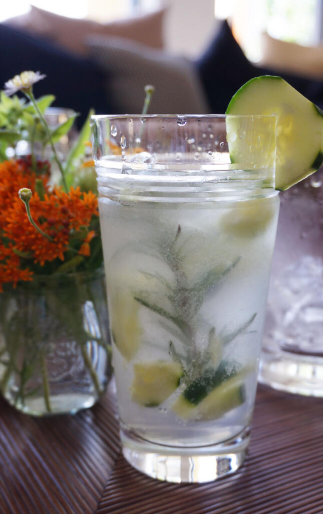 Cucumber Gin Cocktail with Honey tall shot with flowers and cucumber garnish