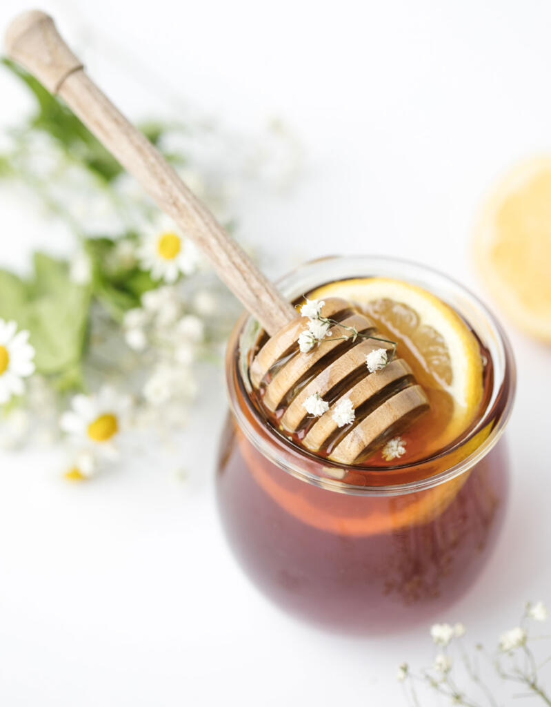 honey with dipper in it on white table with fresh-picked flowers by Heather Barnes