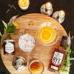 Rye Crush set with Sagamore Rye, fresh squeezed orange juice our honey and candles on wood cutting board