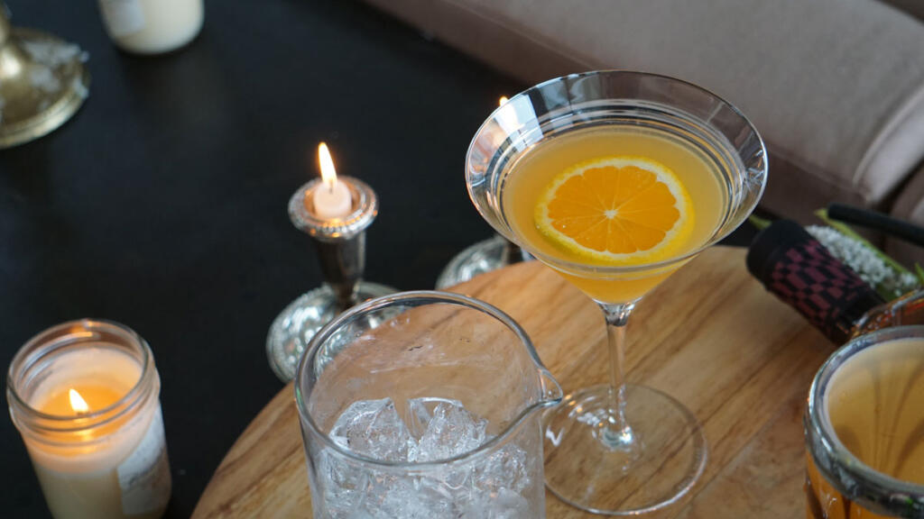 closeup of rye crush in martini glass and lit candle on wood board with ice
