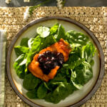Blueberry BBQ Sauce on salmon on bed of spinach on plate from above with dramatic light