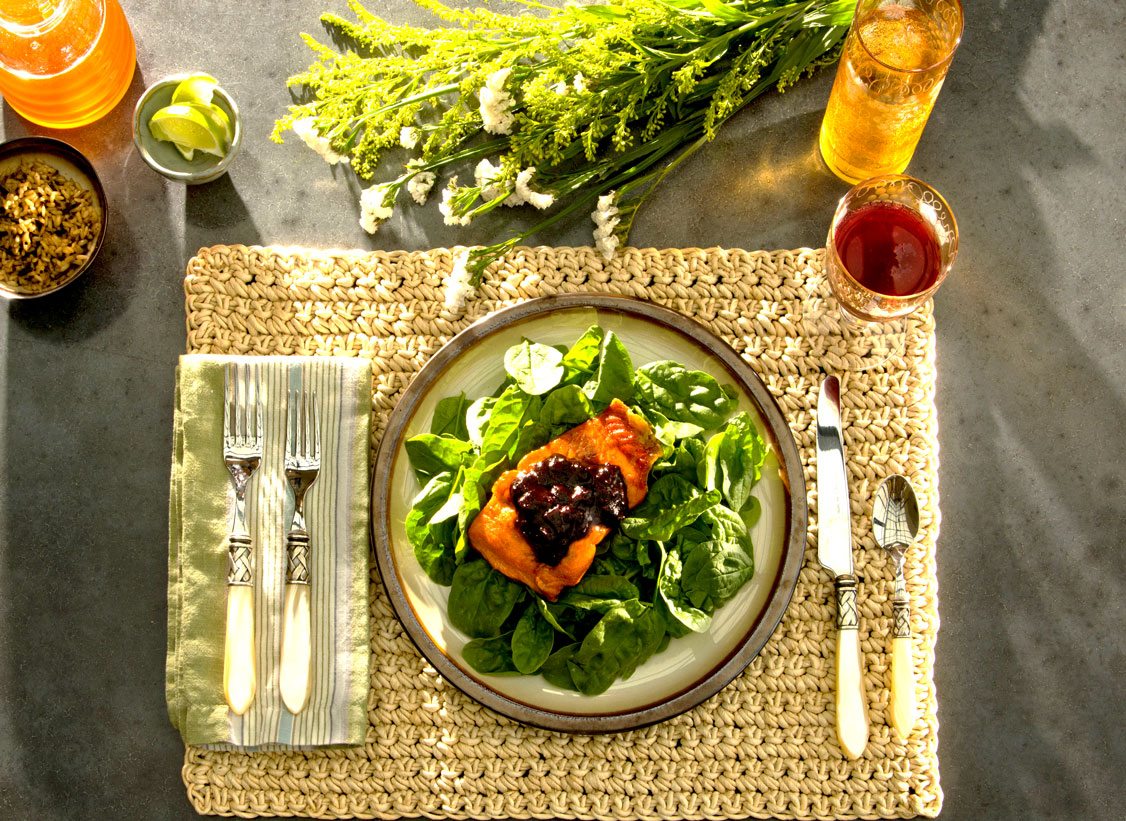 Blueberry BBQ Sauce on salmon on bed of spinach on plate on placesetting from above with dramatic lighting