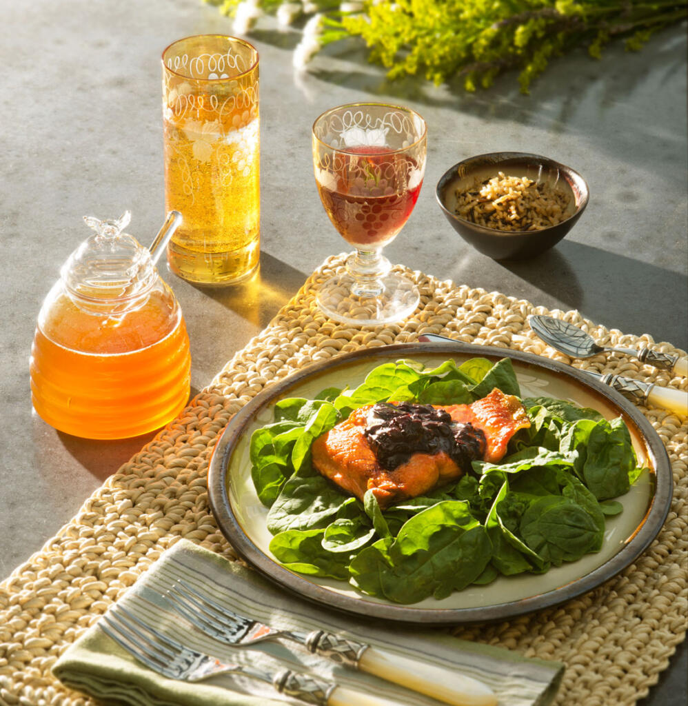 Blueberry BBQ Sauce on salmon on bed of spinach on plate on placesetting from above with dramatic light source