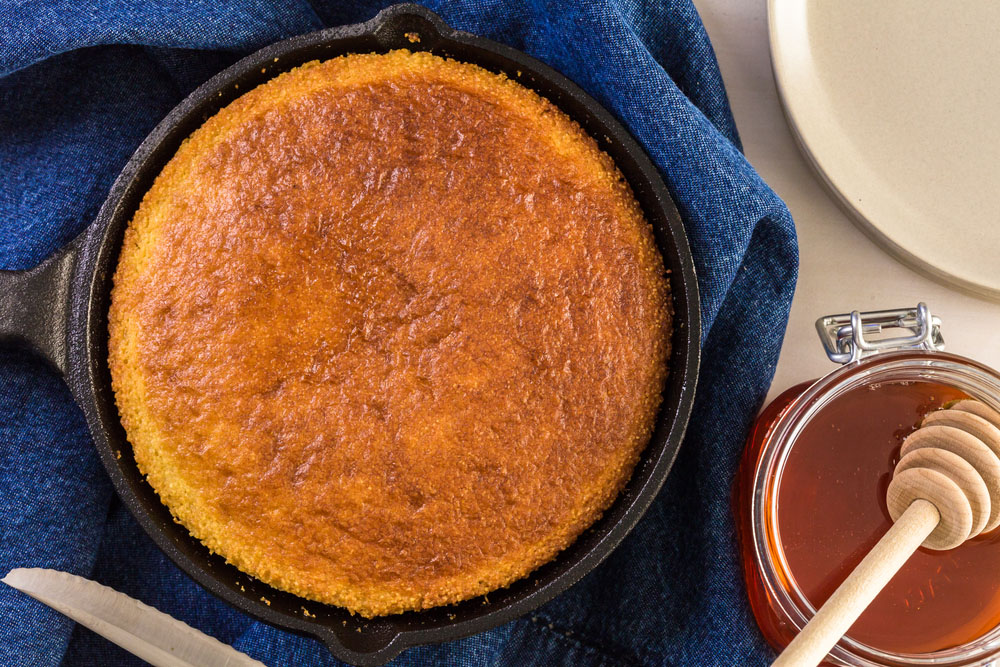 southern cornbread in skillet with honey and almond butter